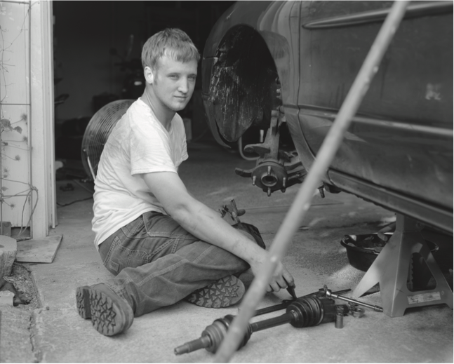 "Figure 10. Jesse Holloway, age 23, Park Hills, Missouri. Jesse replacing the constant-velocity axel on his Ford escort. Carpooling with a neighbor, Holloway makes a 150-mile round trip to St. Louis during the week to work in a welding fabrication shop. He explained, ""There's no real jobs around here."""