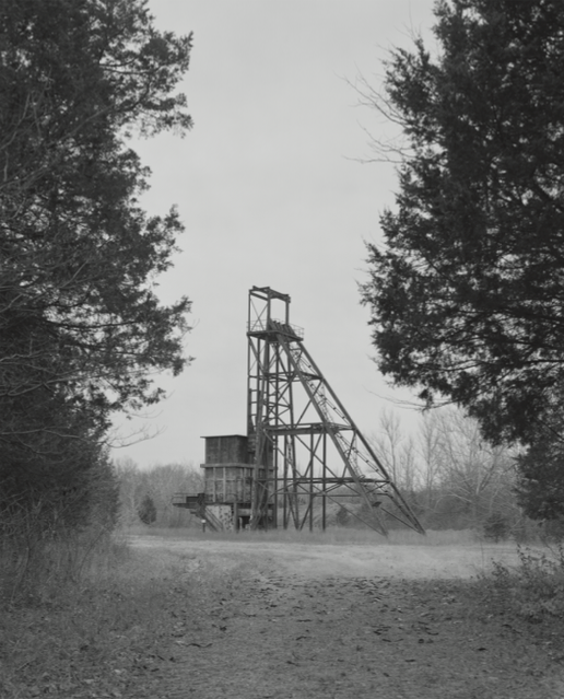 Figure 16. Mining shaft in St. Joe State Park, Missouri. Mineshaft #25 is located on an 8,234-acre plot of land that was donated to the state by the St. Joe Lead Company in 1976 and subsequently became a state park. More than a fourth of the park is covered in highly contaminated mine tailings. Sealed and abandoned, the shaft once ferried miners hundreds of feet below ground. As the underground mining system grew more complex, all shafts and pits were connected to form a single, uni ed mine. Lead ore was shuttled to the surface via more than 240 miles of electric rail line. A handful of abandoned mine shafts remain in areas visible to the public. These shafts and the remediated chat piles that extend through the landscape are the only physical reminders of the mining industry that dominated the Old Lead Belt for more than 100 years.